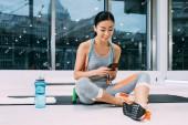 atraktivní asijské dívka sedí na fitness mat a pomocí smartphone ve sportovním centru