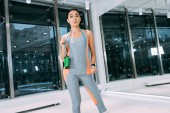 Fotografie attractive asian girl with skipping rope on shoulders looking at camera at gym