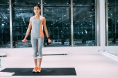 Fotografie attractive asian sportswoman standing on fitness mat and doing exercise with dumbbells at gym