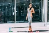 Slim Asijská dívka stojící na fitness mat a dotýká vlasů ve sportovním centru