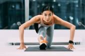 sportovní Asijská sportovkyně strečink nohou na fitness mat ve sportovním centru