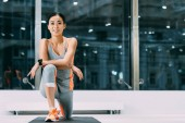 beautiful asian sportswoman smiling and doing stretch exercise on fitness mat in sports center