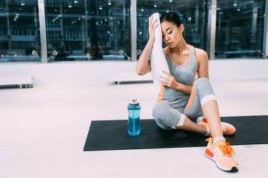 tired asian girl sitting on fitness mat and wiping forehead with white towel at modern gym