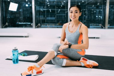 smiling asian sportswoman sitting on fitness mat and touching fitness tracker at gym