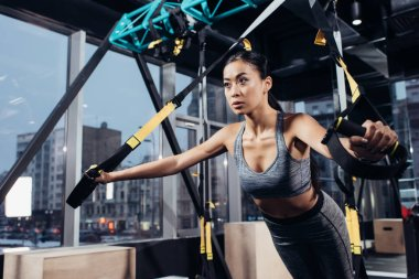 attractive asian girl training with resistance bands at gym