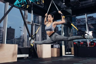 athletic asian sportswoman doing split with resistance bands in fitness center