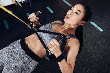 close up view of attractive asian sportswoman exercising with resistance bands at gym