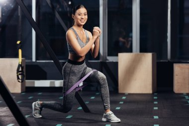 smiling asian girl doing lunges with rubber resistance bands at gym