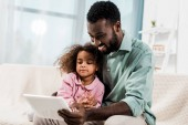 Fotografie lächelnder afrikanisch-amerikanischer Vater und Kind mit digitalem Tablet auf der Couch