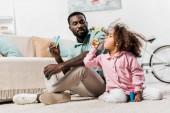 afrikai-amerikai családi ül a padlóra, és fúj a szappanbuborékok