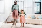 Fotografie Šťastný otec afroamerické a rozkošná dcera tančí v růžové tutu sukně