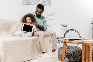 african american father and daughter sitting on couch in living room with digital tablet
