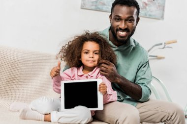 african american father and daughter sitting on couch with digital tablet and looking at camera