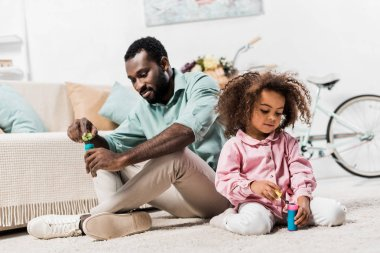 African american father and daughter sitting on floor, making soap bubbles and looking down stock vector