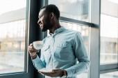 s úsměvem africké americké muž držící šálek kávy a při pohledu z okna