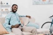 boldog afrikai amerikai férfi ült a kanapén távirányító