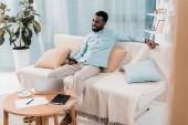 afro-amerikai ember tévénézés, és ül a nappaliban kanapé