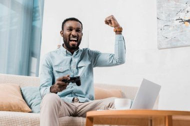 african american man rejoicing while playing video game