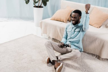 african american man playing video and rejoicing in living room