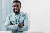 Američan Afričana muž při pohledu na fotoaparát a usmívá se v obývacím pokoji
