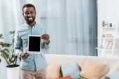 Američan Afričana muž zobrazuje digitální tabletu a usmívá se v obývacím pokoji