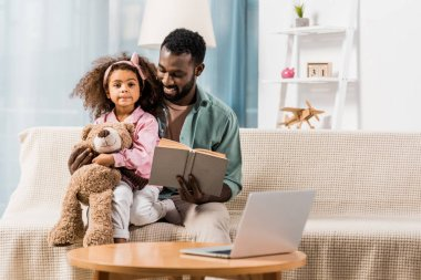 african american father reading book with daughter in living room