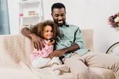Fényképek afro-amerikai apa átölelve lányom, miközben nézi a televíziót, a nappali
