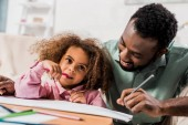african american man drawing with daughter in living room
