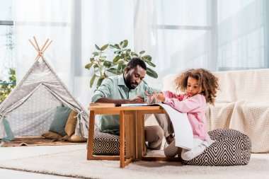 african american dad helping daughter with drawing in living room