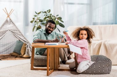 african american father helping daughter with drawing in living room