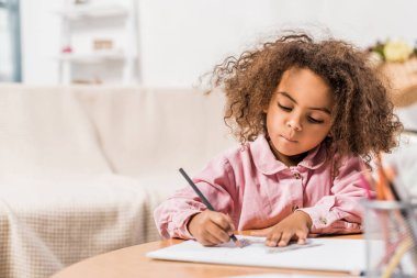 serious african american kid drawing on paper with color pencil in living room