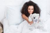magas, szög, kilátás a fiatal afroamerikai nő szóló ágyban, és bemutatja a teddy bear otthon
