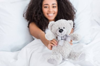 Selective focus of african american girl laying in bed and showing teddy bear at home stock vector