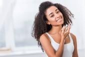 Fényképek vidám afro-amerikai lány göndör használ parfüm otthon