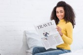 Photo curly african american girl reading travel newspaper at home