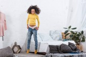 pretty african american girl putting on jeans in bedroom at home