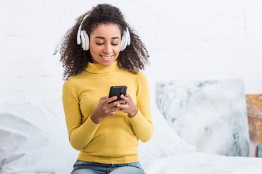 attractive young woman in headphones listening music with smartphone at home