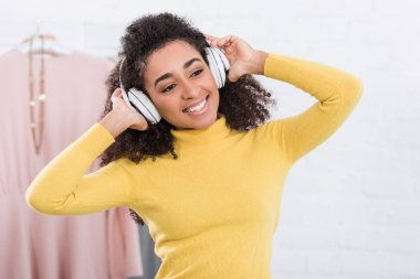 happy young african american woman listening music in headphones