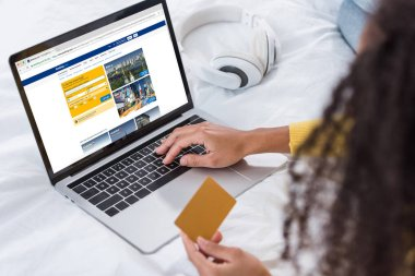 Cropped image of woman holding credit card and using laptop with booking on screen stock vector