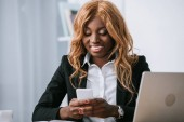 beautiful african american businesswoman using smartphone in office