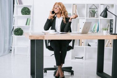 attractive african american businesswoman talking on smartphone and sitting with crossed legs in office