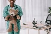 Fotografie oříznutý pohled s úsměvem africké americké zdravotní sestra drží medvídek světle klinice s mikroskopem
