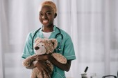 Fotografie Veselá africká americká sestra drží medvídek světle klinice