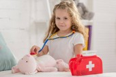 Photo adorable kid examining rabbit toy with stethoscope in children room and looking at camera