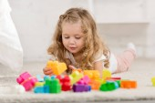 surface level of adorable kid playing with colored plastic constructor on carpet in children room