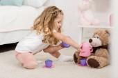 Fotografie Rozkošné dítě hraje s plyšovým medvědem na podlaze v pokoji dětí