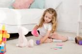Rozkošné dítě hraje s králík hračka a plastové kelímky v místnosti dětí
