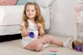 Rozkošné dítě hraje s kelímky na podlaze v pokoji dětí