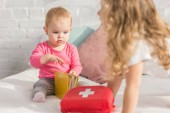 selective focus of adorable kid holding book in children room