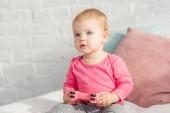 Rozkošné dítě v růžové košili zvedl růžový joysticku na posteli u dětí pokoj a při pohledu